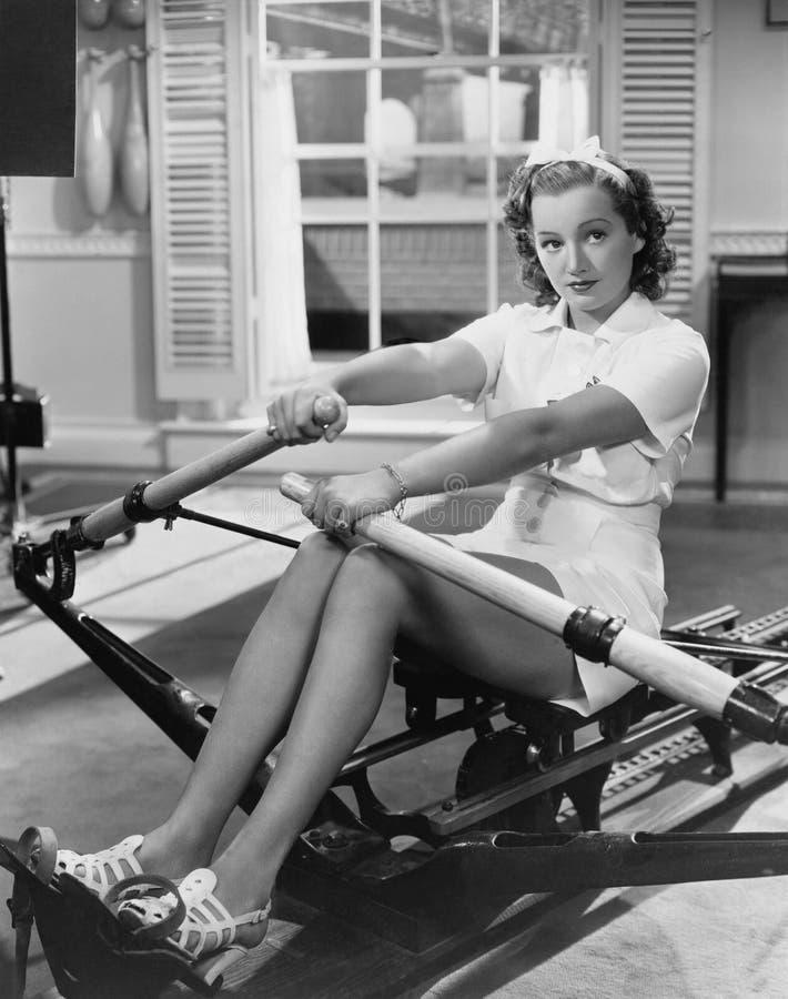 Женщина используя машину rowing (все показанные люди более длинные живущие и никакое имущество не существует Гарантии поставщика  стоковые фото