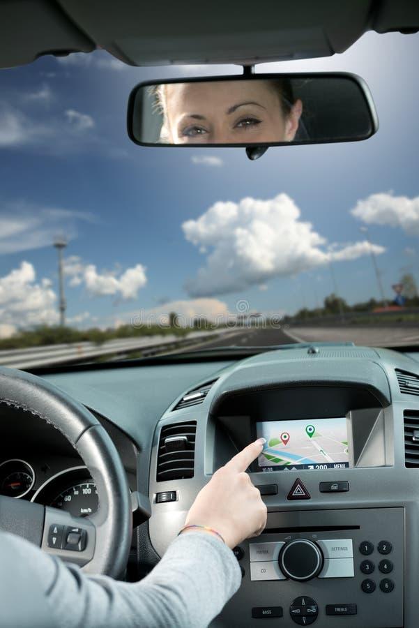 Женщина используя навигатора gps в автомобиле стоковое фото