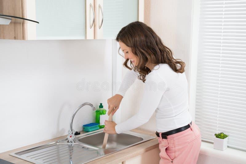 Женщина используя плунжер в раковине стоковое фото