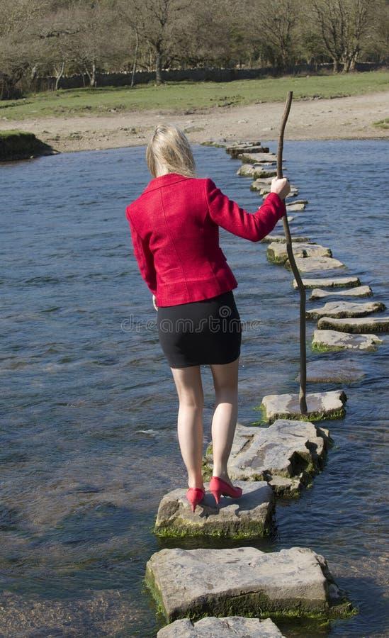 Женщина используя стартовые площадки для того чтобы пересечь реку стоковое фото