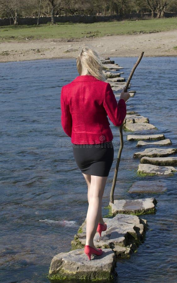 Женщина используя стартовые площадки для того чтобы пересечь реку стоковое изображение rf