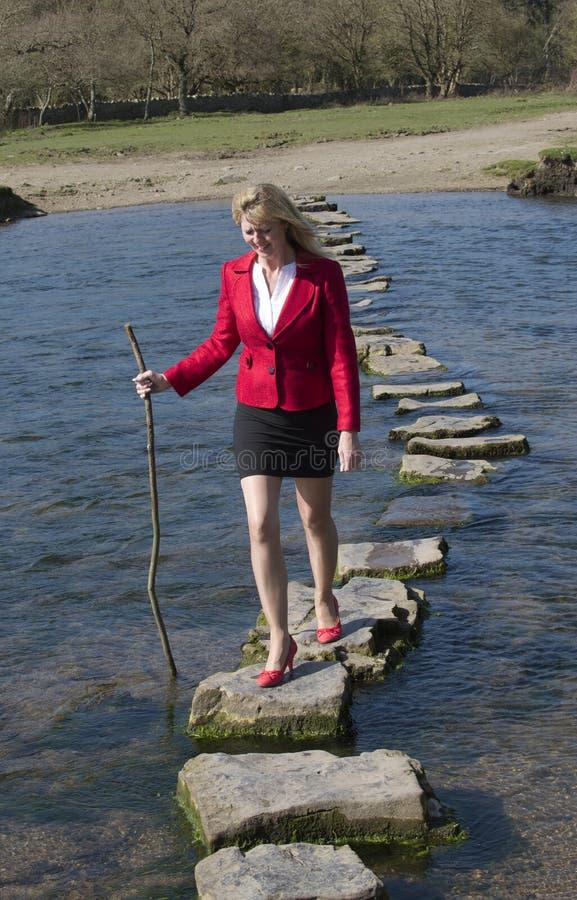 Женщина используя стартовые площадки для того чтобы пересечь реку стоковые фотографии rf