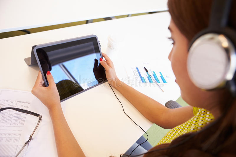 Женщина используя таблетку и наушники цифров в студии дизайна стоковые фотографии rf