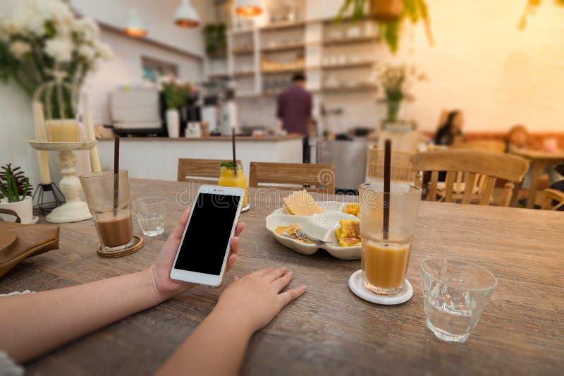 Женщина используя телефон в кафе стоковая фотография rf