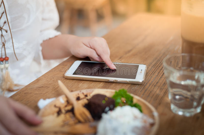 Женщина используя телефон в кафе стоковое изображение rf