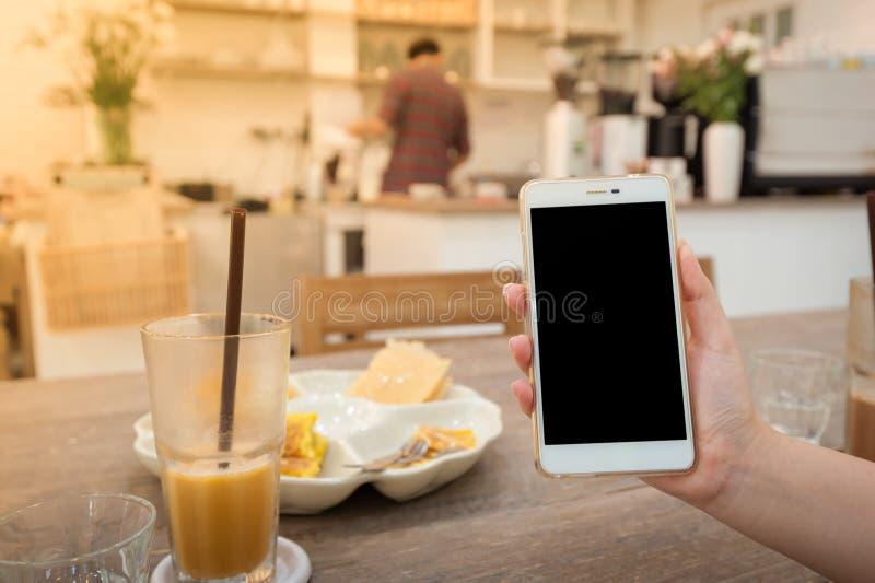 Женщина используя телефон в кафе стоковые изображения rf