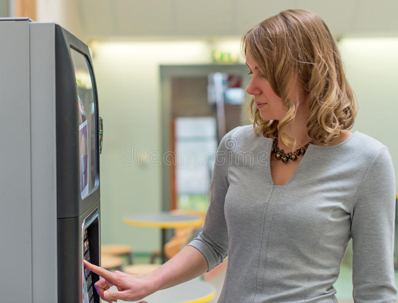 Женщина используя торговый автомат кофе стоковые фотографии rf