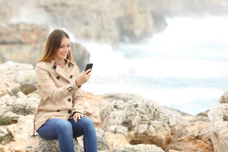 Женщина используя умный телефон в зиме на пляже стоковые изображения