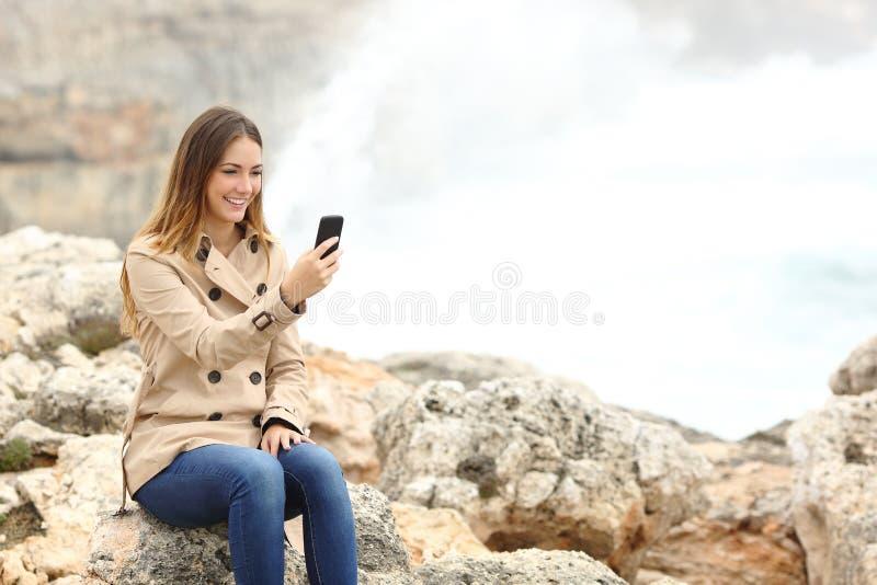 Женщина используя умный телефон на пляже в зиме стоковое изображение