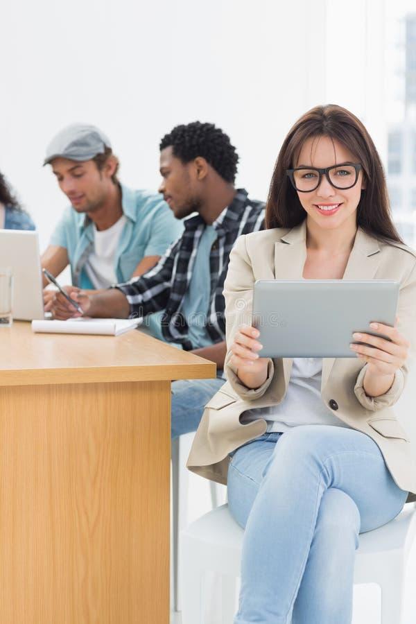 Женщина используя цифровую таблетку с коллегами позади в офисе стоковое изображение