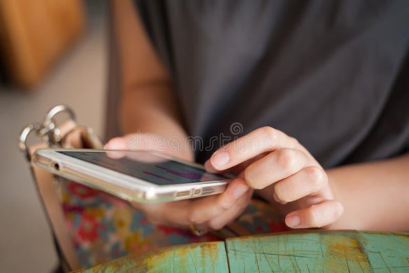 Женщина используя smartphone в кафе стоковое изображение rf