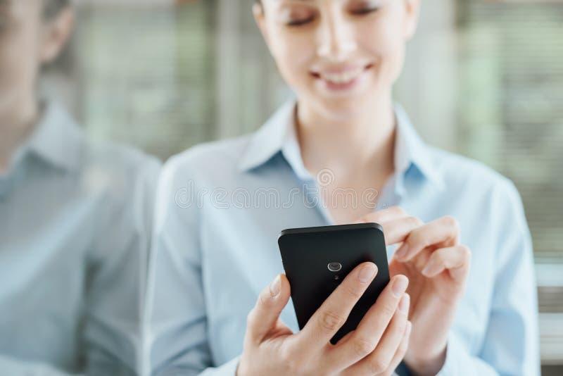 Женщина используя smartphone и полагающся на окне стоковая фотография rf