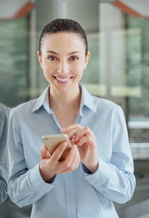 Женщина используя smartphone и полагающся на окне стоковое изображение