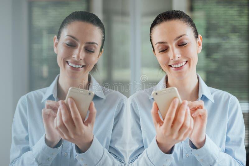 Женщина используя smartphone и полагающся на окне стоковое фото rf