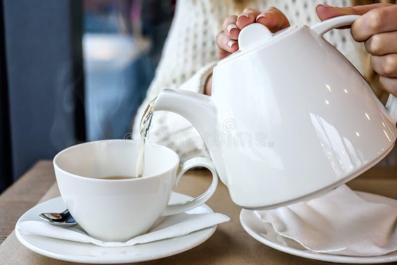 Женщина лить чашку горячего испаряясь чая в ресторане Отдых зимы, холод, питье стоковые изображения