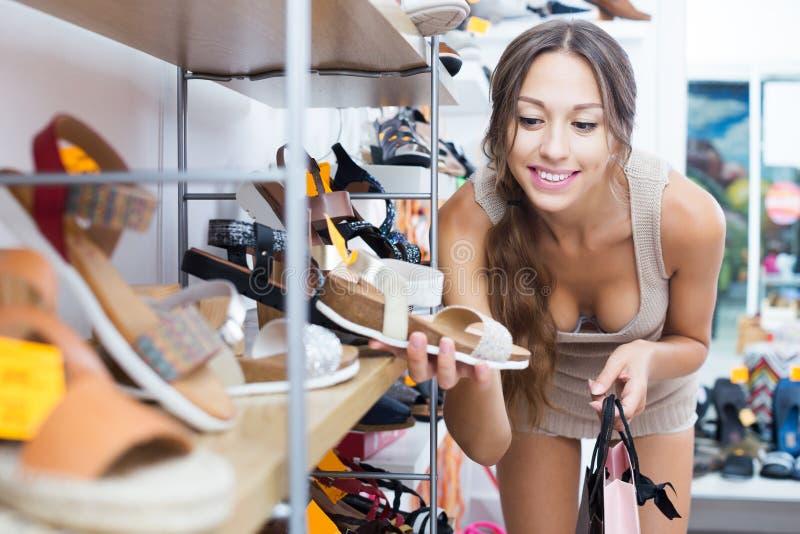Женщина ища новые ботинки стоковое изображение