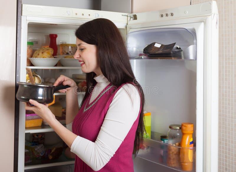 Женщина ища для что-то в холодильнике дома стоковые изображения