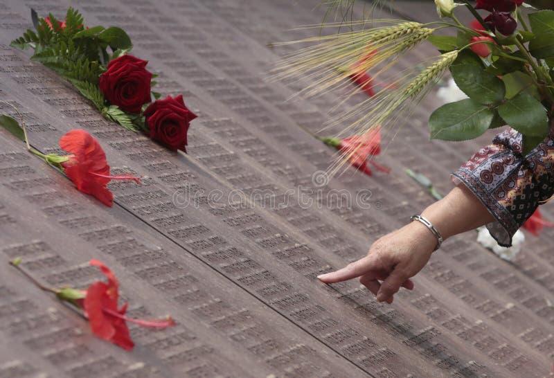 Женщина ищет имя ее родственников в могиле стены памяти мемориальной в mallorca стоковые изображения
