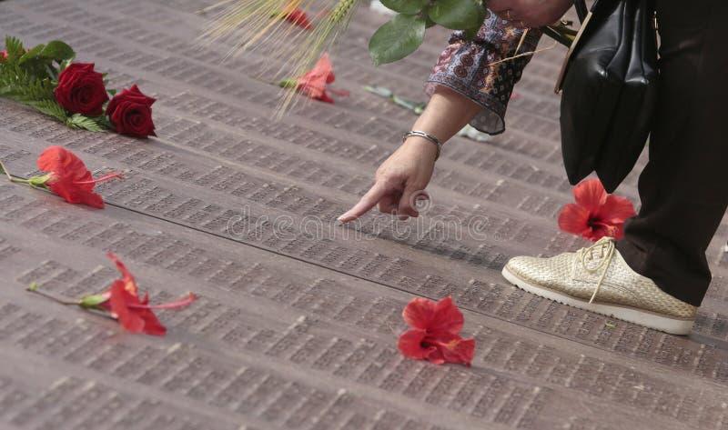 Женщина ищет имя ее родственников в могиле стены памяти мемориальной в mallorca широко стоковое фото rf