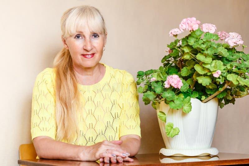 Женщина и большая цветя пеларгония внутри помещения стоковое изображение rf
