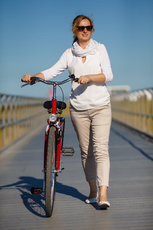 Женщина и велосипед в городе стоковые фото