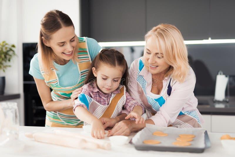 Женщина и ее мать учащ девушке как сварить домодельные булочки Они положили тесто в прессформы стоковые фото