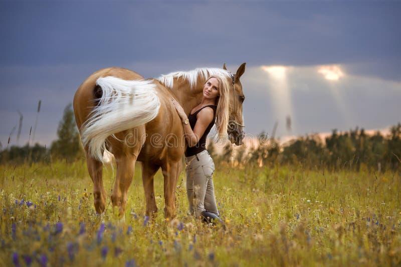 Женщина и золотая лошадь на заходе солнца стоковое фото rf