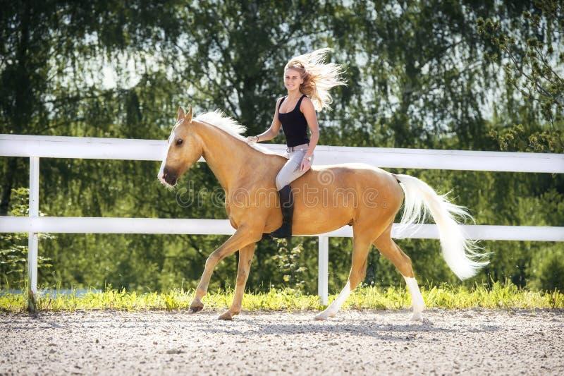 Женщина и золотая лошадь стоковые фото