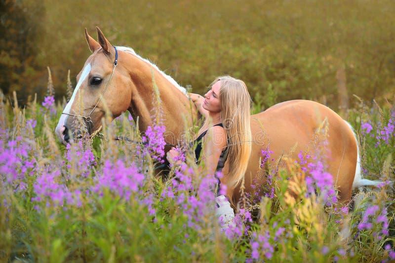 Женщина и золотая лошадь стоковые изображения
