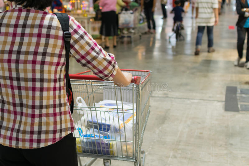 Женщина и магазинная тележкаа стоковые изображения
