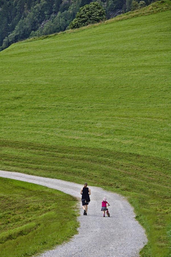 Женщина и маленькая девочка с strider велосипед от задний идти вдоль следа гравия в зеленом поле стоковые изображения rf