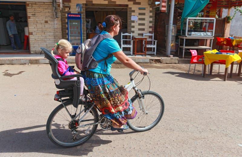 Женщина и маленькая девочка на велосипеде стоковое изображение