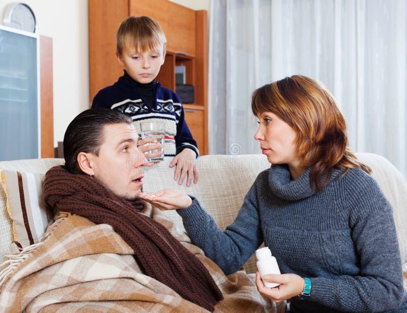Женщина и мальчик заботя для больного человека стоковое фото