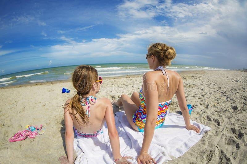 Женщина и дочь ослабляя на красивом пляже совместно на каникулах стоковые фото
