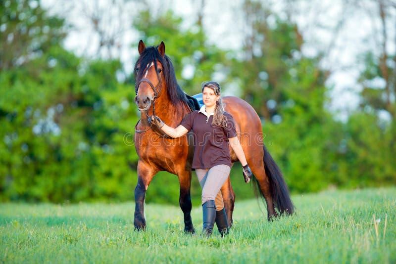 Женщина и лошадь идя в поле стоковое фото