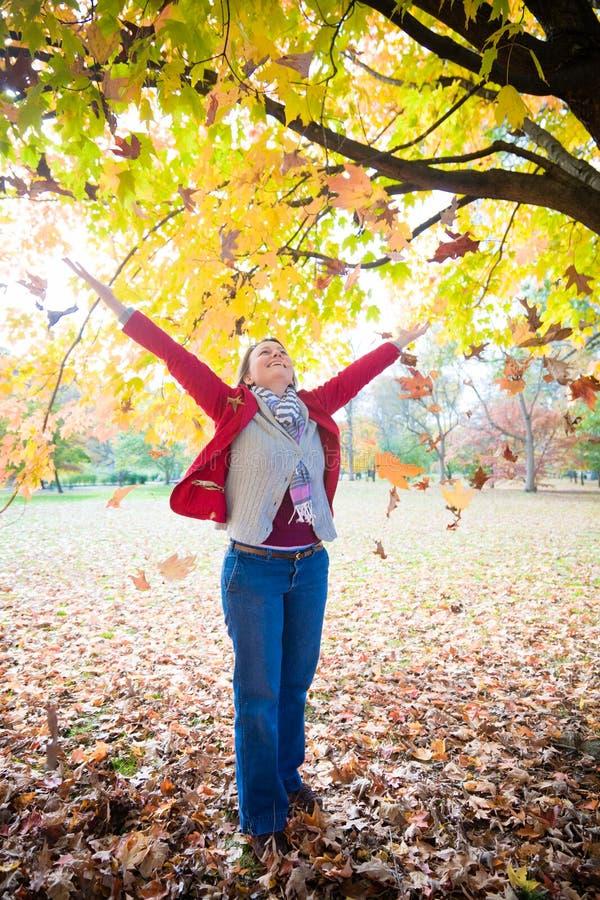 Женщина и падая листья стоковые фото