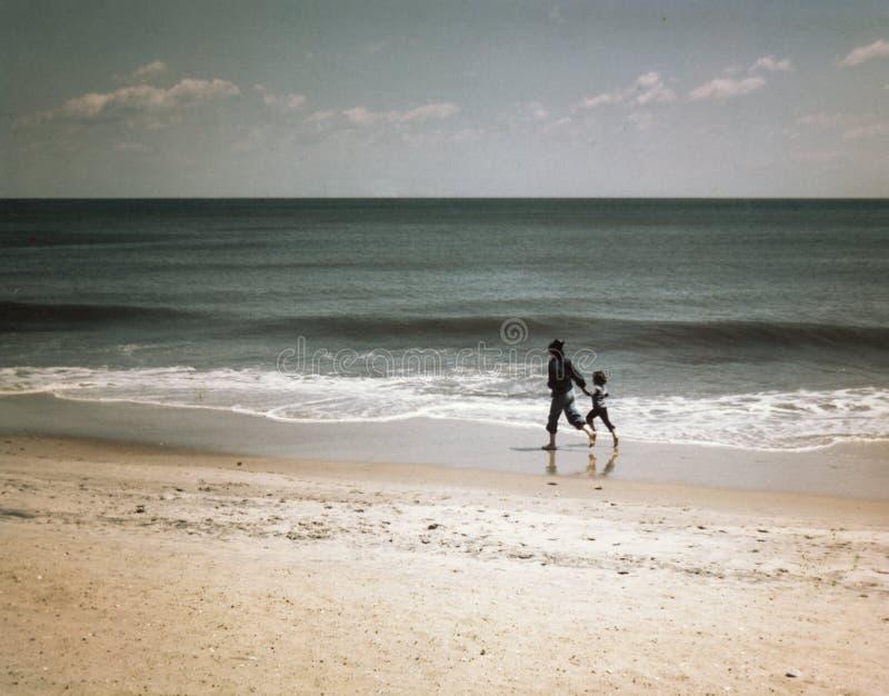 Женщина и ребенок бежать barefoot на пляже стоковое изображение rf