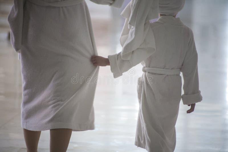Женщина и ребенок идут в белые купальные халаты стоковое изображение
