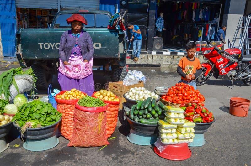 Женщина и ребенок продавая овощи в Гватемале стоковые фото