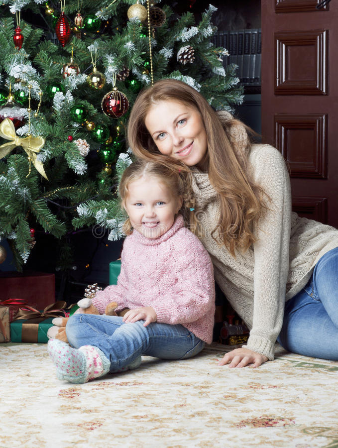 Женщина и ребенок сидя около рождественской елки стоковая фотография rf