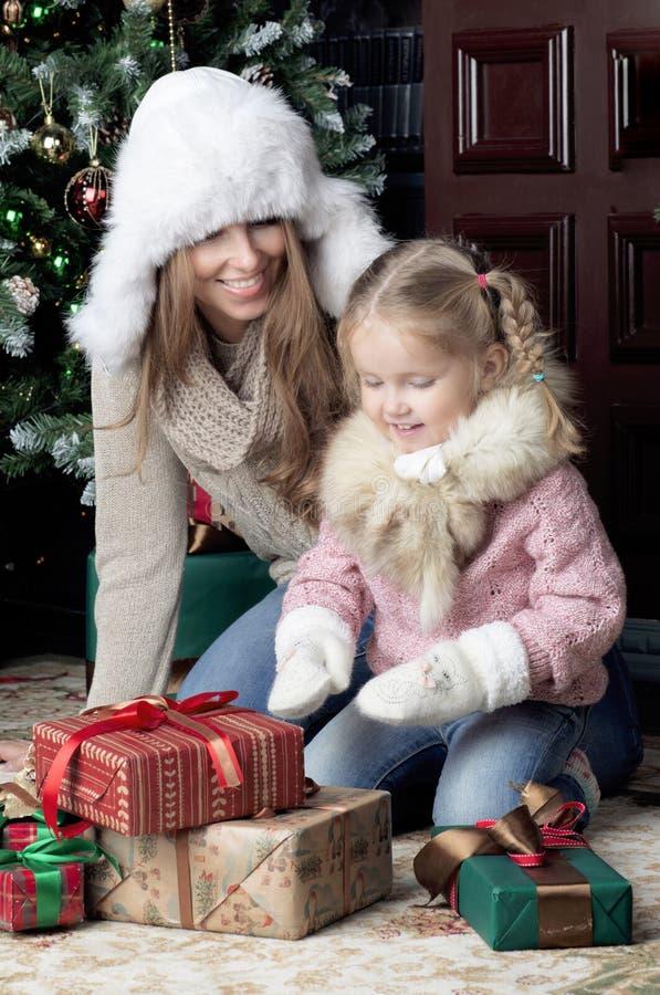Женщина и ребенок сидя около рождественской елки стоковые изображения