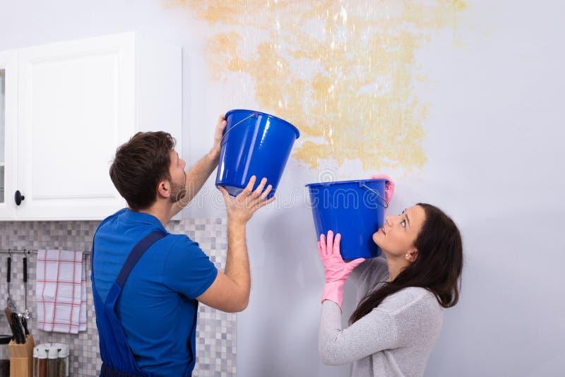 Женщина и ремонтник с собирать воду от поврежденного потолка стоковые фото