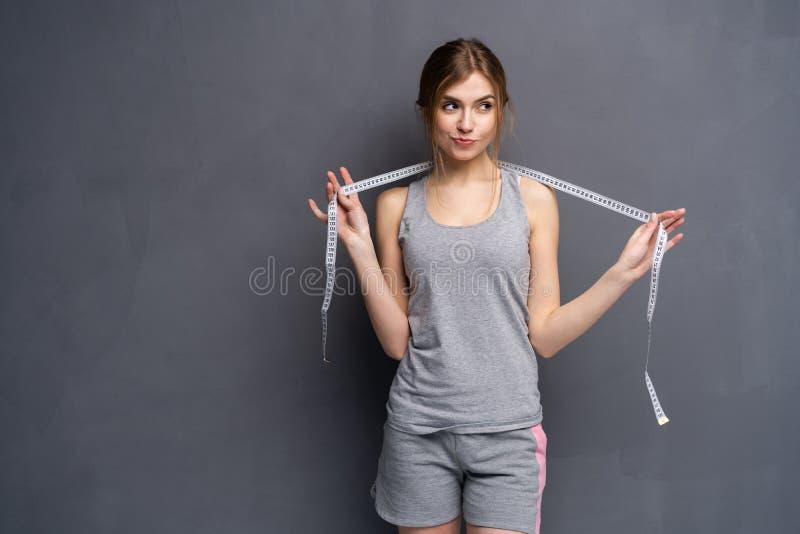 Женщина и рулетка Молодой, sporty, пригонка и красивый девушка с измеряя лентой стоковая фотография rf