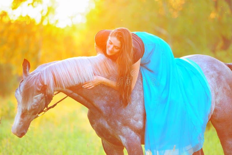 Женщина и серая лошадь в золотом свете стоковая фотография rf
