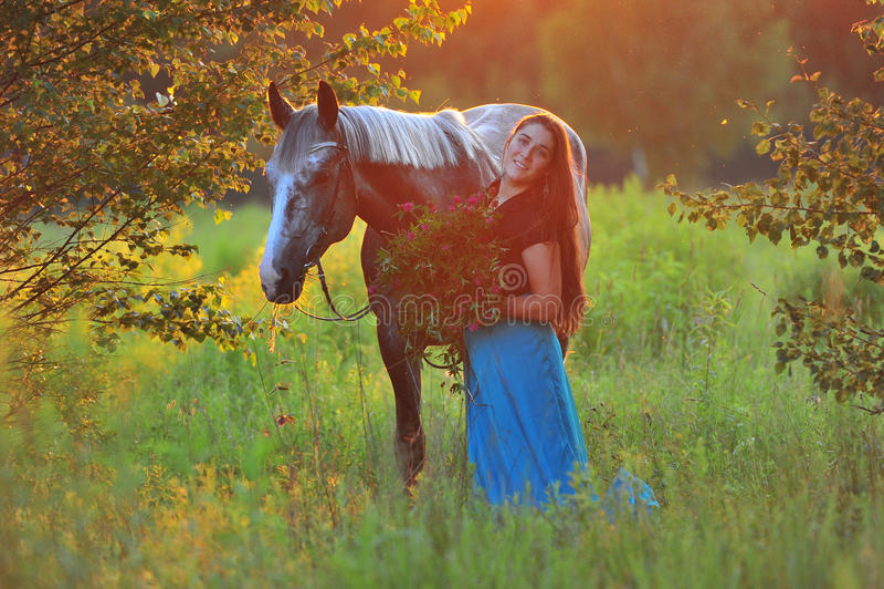 Женщина и серая лошадь в золотом свете стоковая фотография