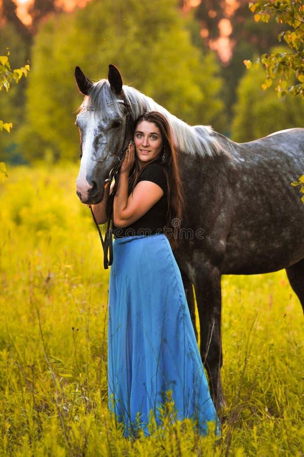 Женщина и серая лошадь стоковое фото