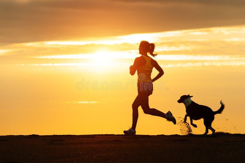 Женщина и собака бежать на пляже на заходе солнца стоковая фотография rf