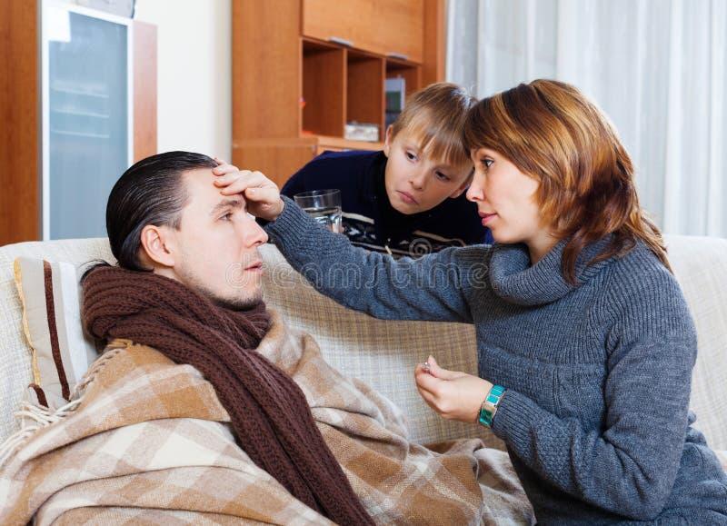 Женщина и сын заботя для нездорового человека стоковое фото rf