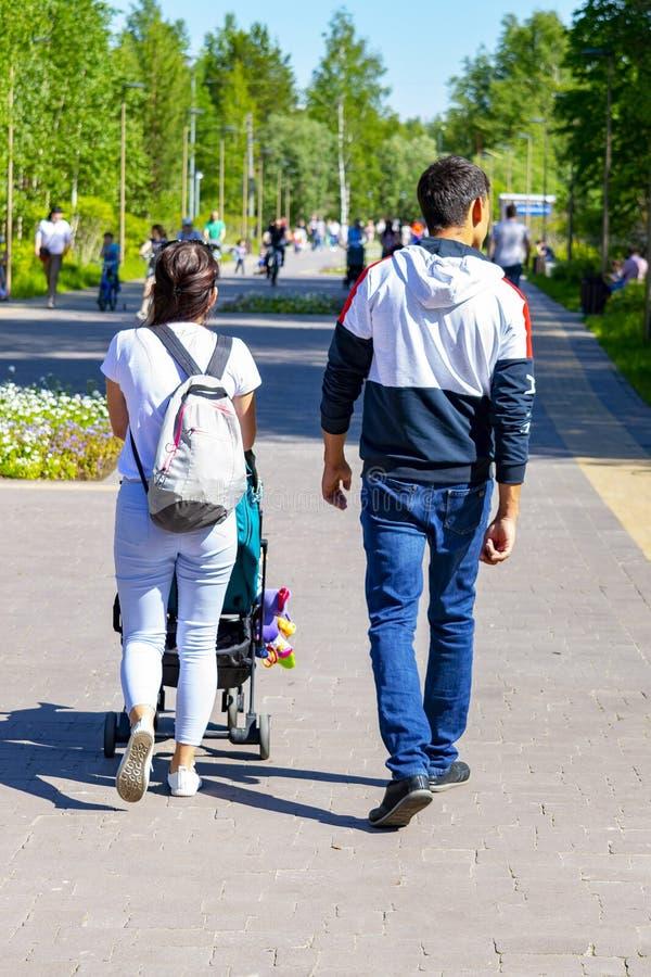 Женщина и человек идут вдоль пути в парке Женщина свертывает экипажа ребенка r стоковые изображения rf