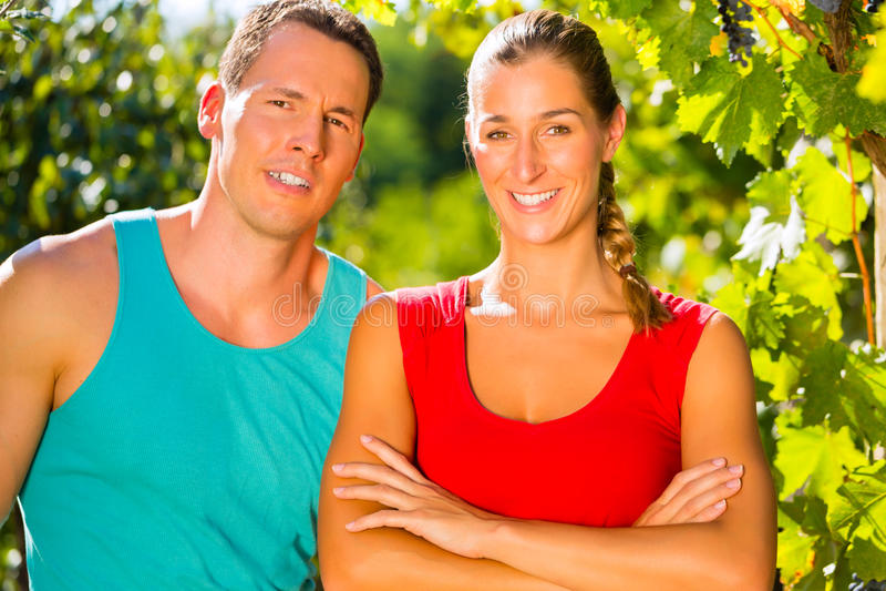 Женщина и человек стоя в винограднике стоковые изображения